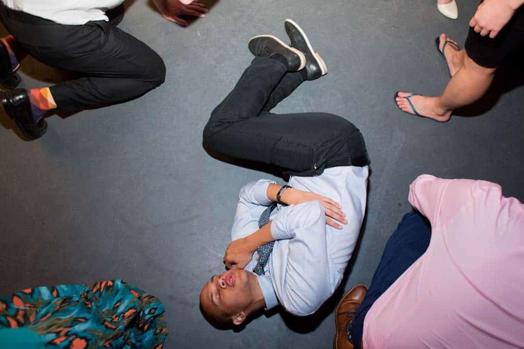 A wedding guest lies down on a dance floor during a wedding reception at Green Building Brooklyn, NJ