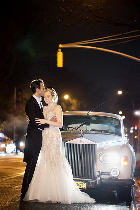 Bride and groom in front of 1963 Rolls Royce on 5th Ave, NYC after a wedding reception and rain. Allure Couture