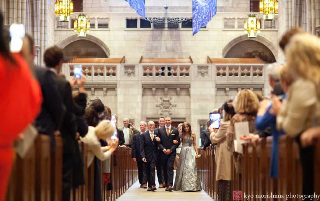 Groom walks down the aisle flanked by parents during Princeton University Chapel wedding
