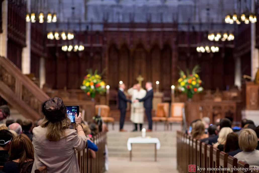 A guest photographs wedding ceremony at altar of Princeton University chapel