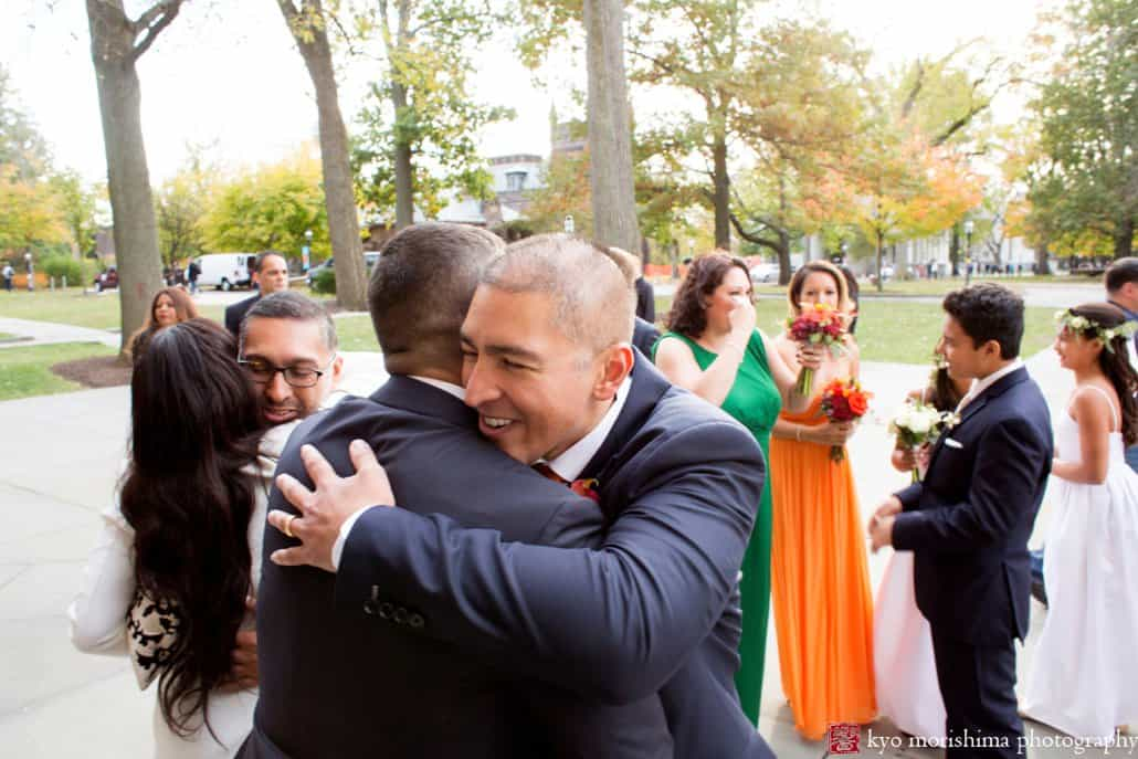 Groom embraces family member after Princeton University Chapel wedding in October