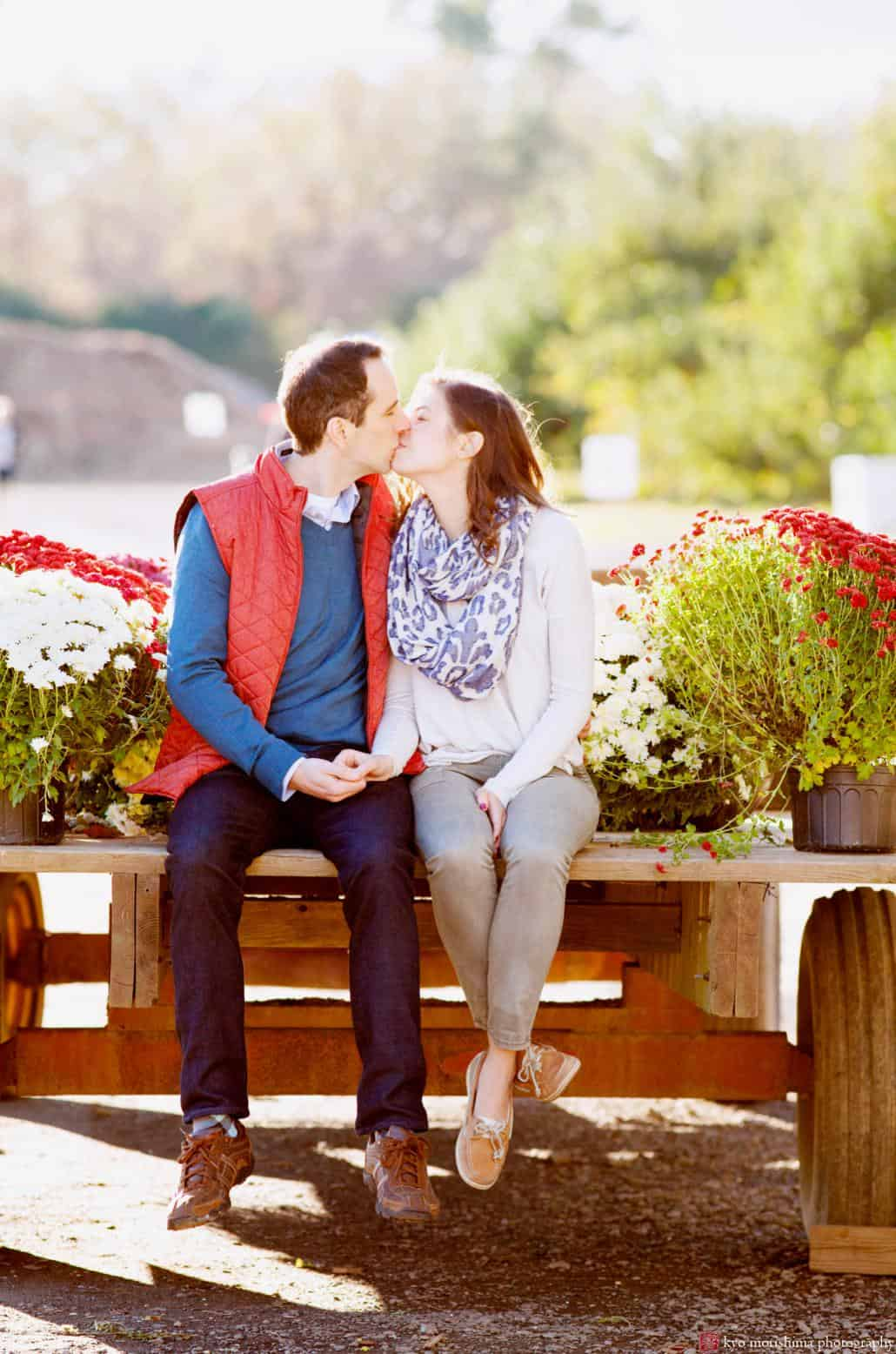 A couple sits on wooden crates surrounded by mums and kisses during their Terhune Orchards engagement shoot. One of NJ's best photoshoot locations, Terhune Orchards is located in Princeton.