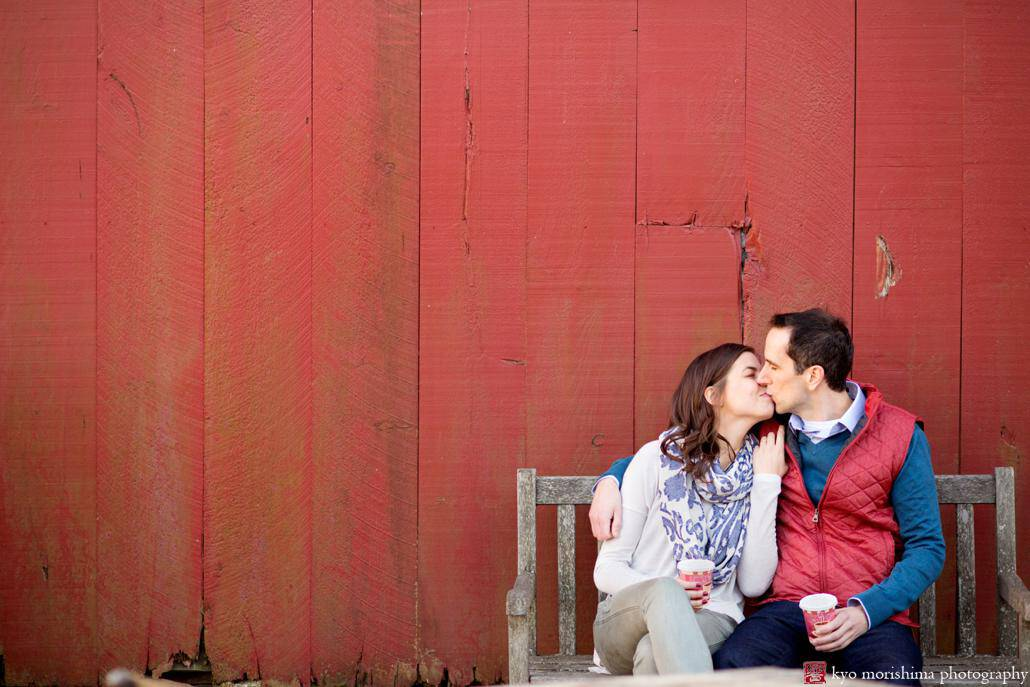 One of the best photography spots in NJ: the red barn at Terhune Orchards in Princeton. In this engagement picture, a couple hold cups of steaming hot apple cider and give each other a kiss.