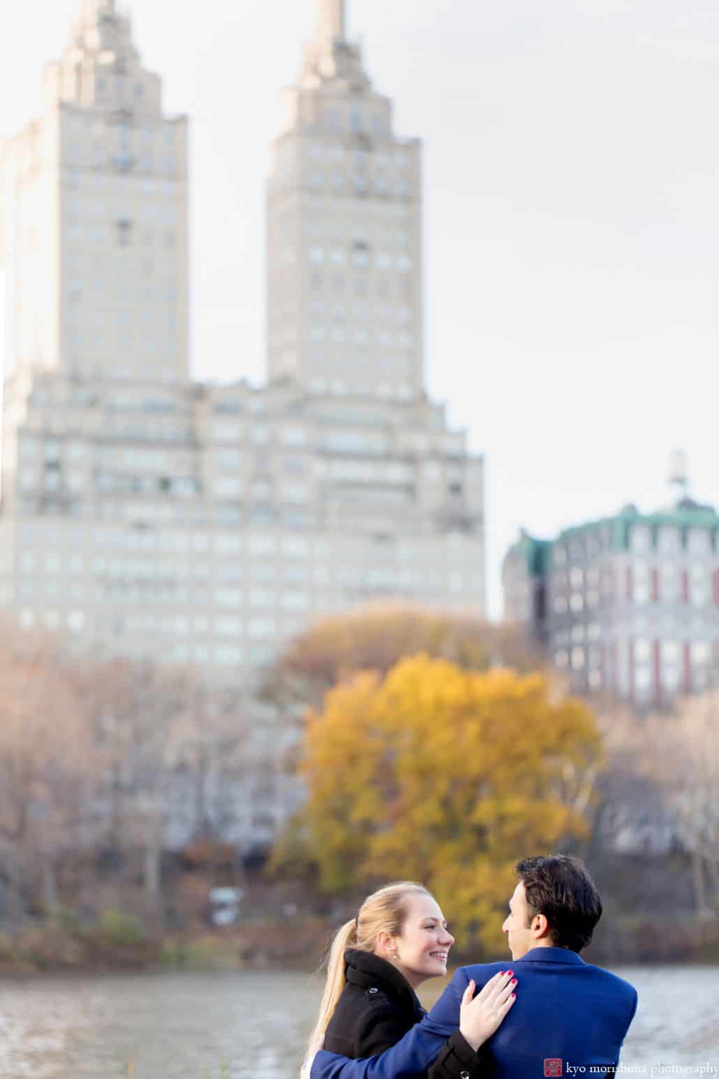 Central Park engagement photos at the pond in winter with last remnants of fall foliage visible.