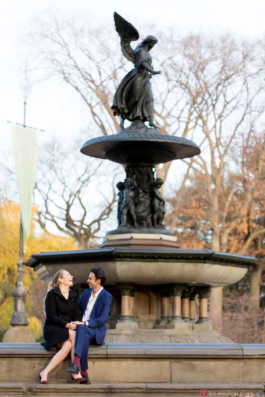 Central Park engagement photo at Bethesda Fountain; woman wears black jacket and man wears royal blue suit.