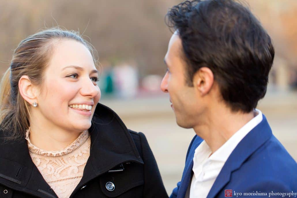 Couple laughs together in wintertime Central Park engagement portrait