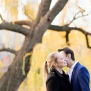 Engagement photo kiss with yellow-leaved willow tree in the background at Central Park