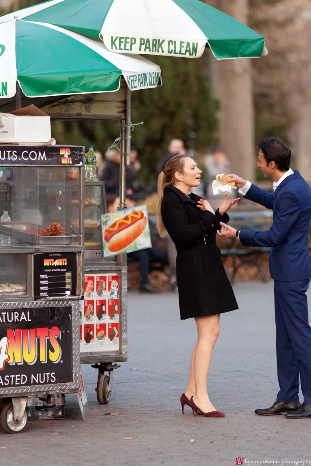 Funny Central Park engagement photo as man offers his fiancée a hot dog