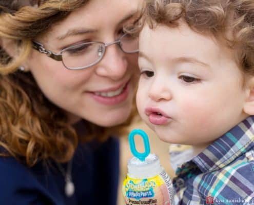 Candid family photographer central New Jersey: child blows bubbles with mom