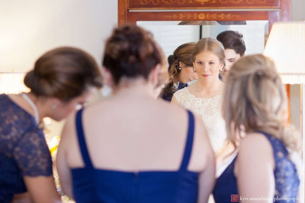 Bride gazes into mirror as she gets ready for wedding surrounded by her bridesmaids; Bernards Inn wedding photos by Kyo Morishima