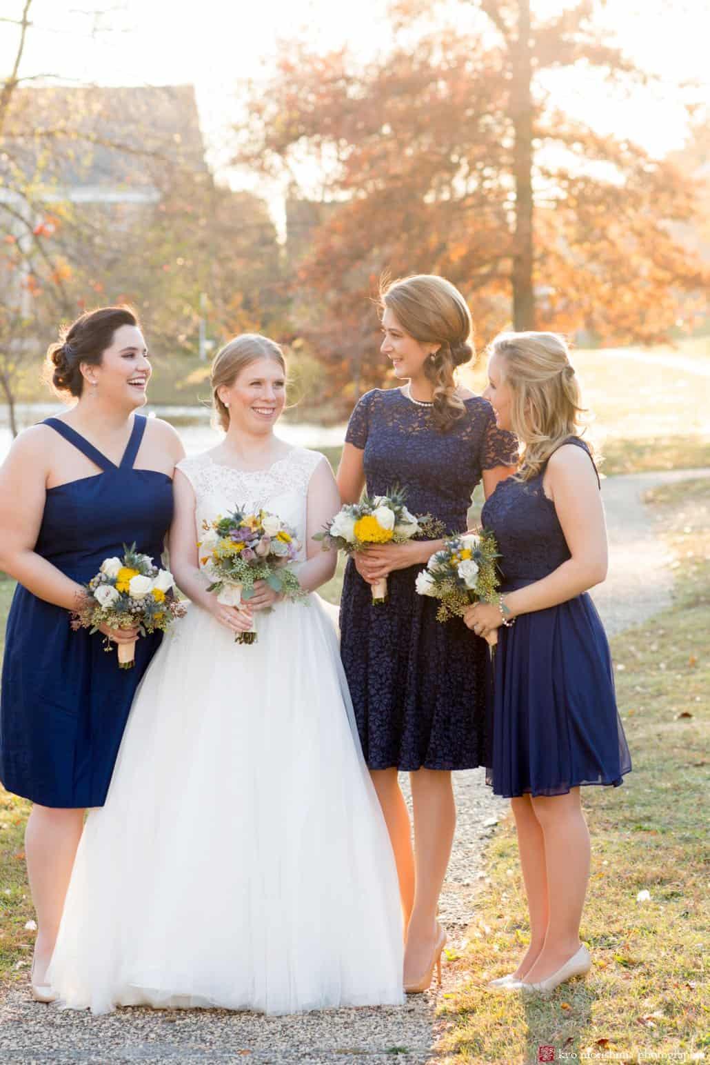 Bride holding yellow, mauve, grey and moss green fall wedding bouquet stands with bridesmaids wearing navy blue dresses in this Bernards Inn fall wedding party portrait
