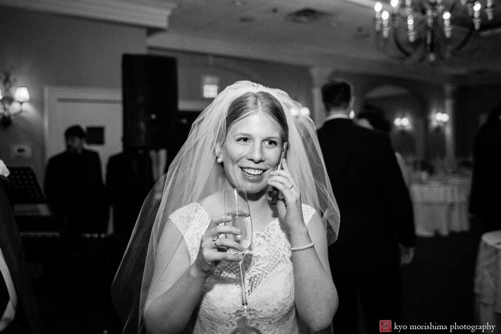 Bride calls a loved one on iPhone immediately after Bernards Inn wedding ceremony; black and white documentary wedding photo by Kyo Morishima