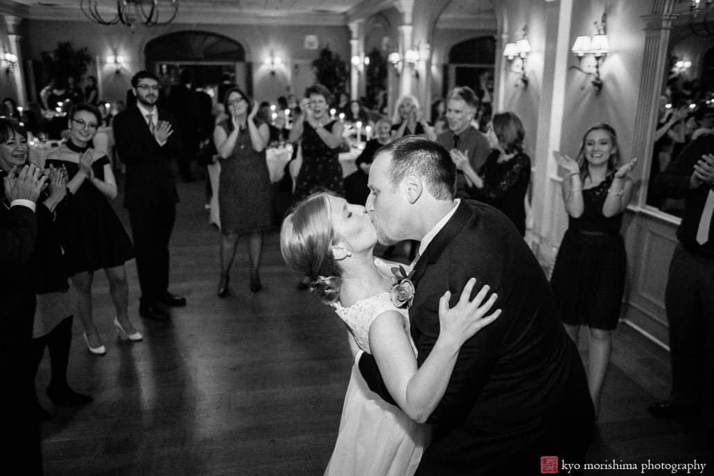 Bride and groom kiss on the dance floor as guests look on, with music by Princeton-based wedding band Franklin & Allison Orchestra. Bernards Inn wedding photography by Kyo Morishima