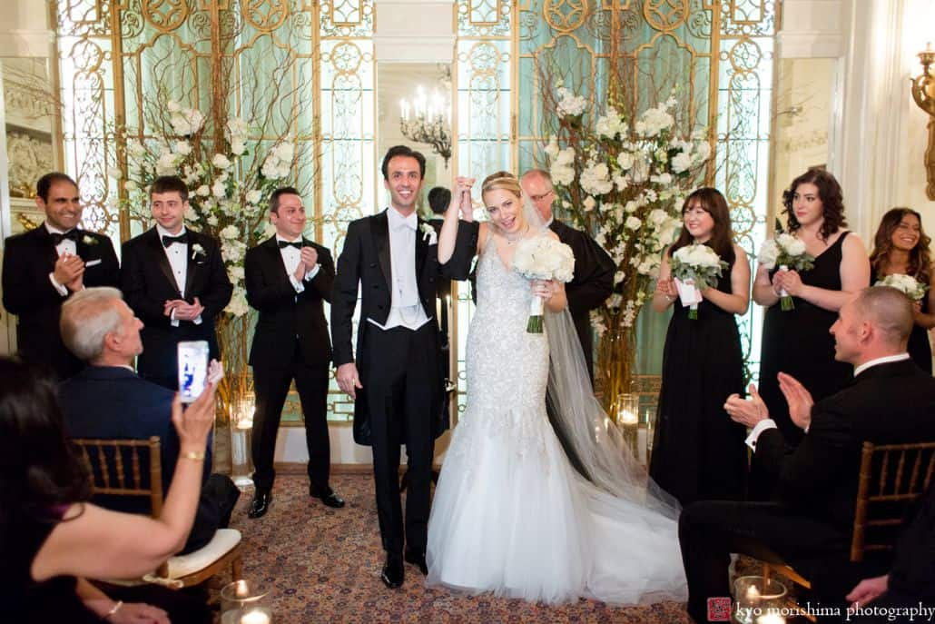 Bride and Groom walk down the aisle for the first time as man and wife while guests and wedding party applaud at the Lotos Club in NYC. Wedding Photography by Kyo Morishima.