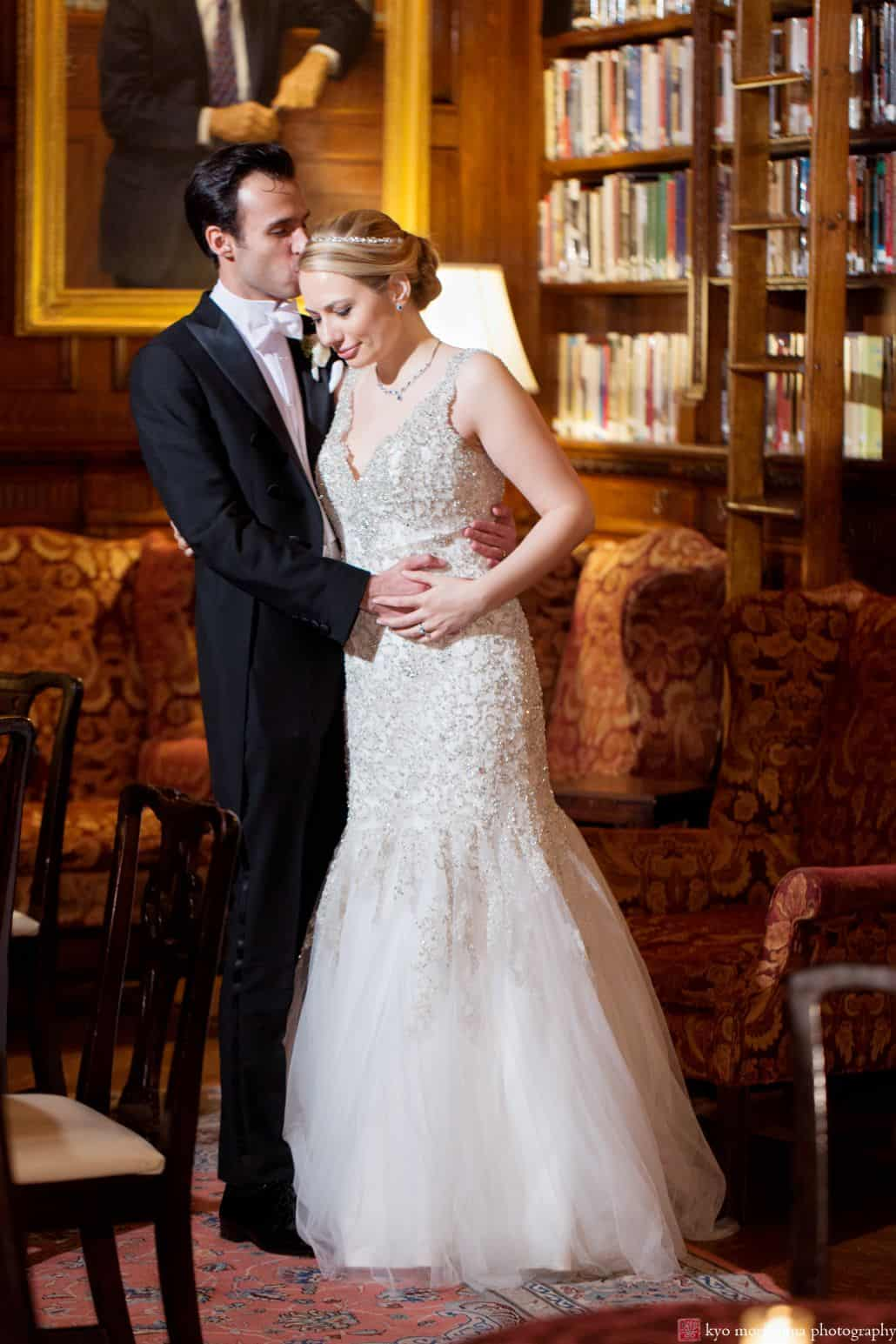 Groom kisses his bride's head in the Library of the Lotos Club in NYC. Bride wears Allure Couture wedding gown. Wedding Photography by Kyo Morishima.