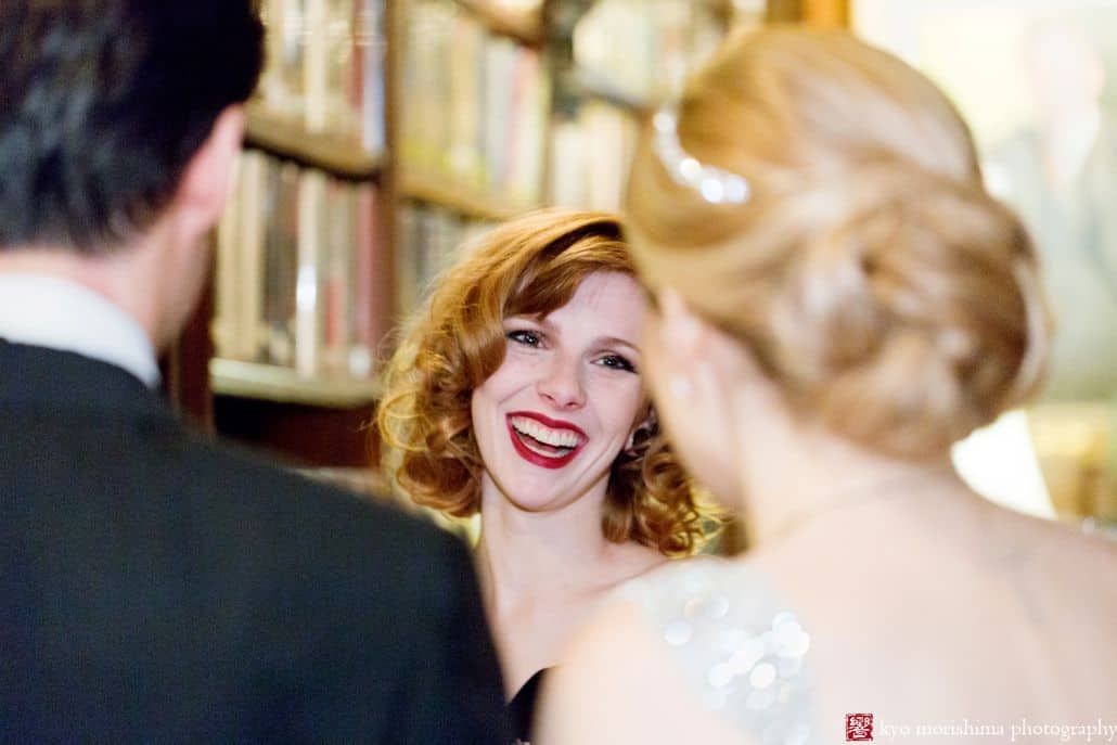 Bride's maid smiles at the bride and groom in the Library of the Lotos Club in NYC. Wedding Photography by Kyo Morishima.