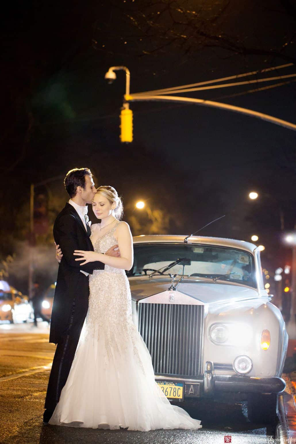 Bride and groom embrace in front of a 1955 Rolls Royce for an evening wedding photo in NYC at the Lotos Club. Lotos Club Wedding Photography by Kyo Morishima.