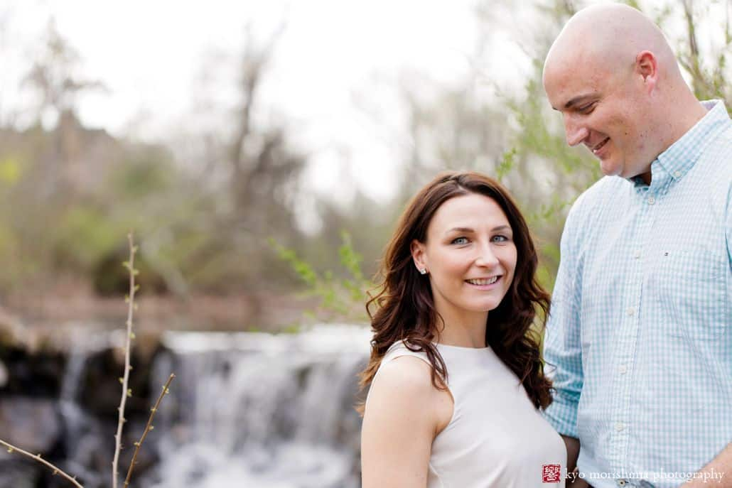 Couple poses for Spring portrait in front of waterfall for Hillsborough, NJ engagement photographer.Woman wears white blouse and man wears blue gingham button down shirt.