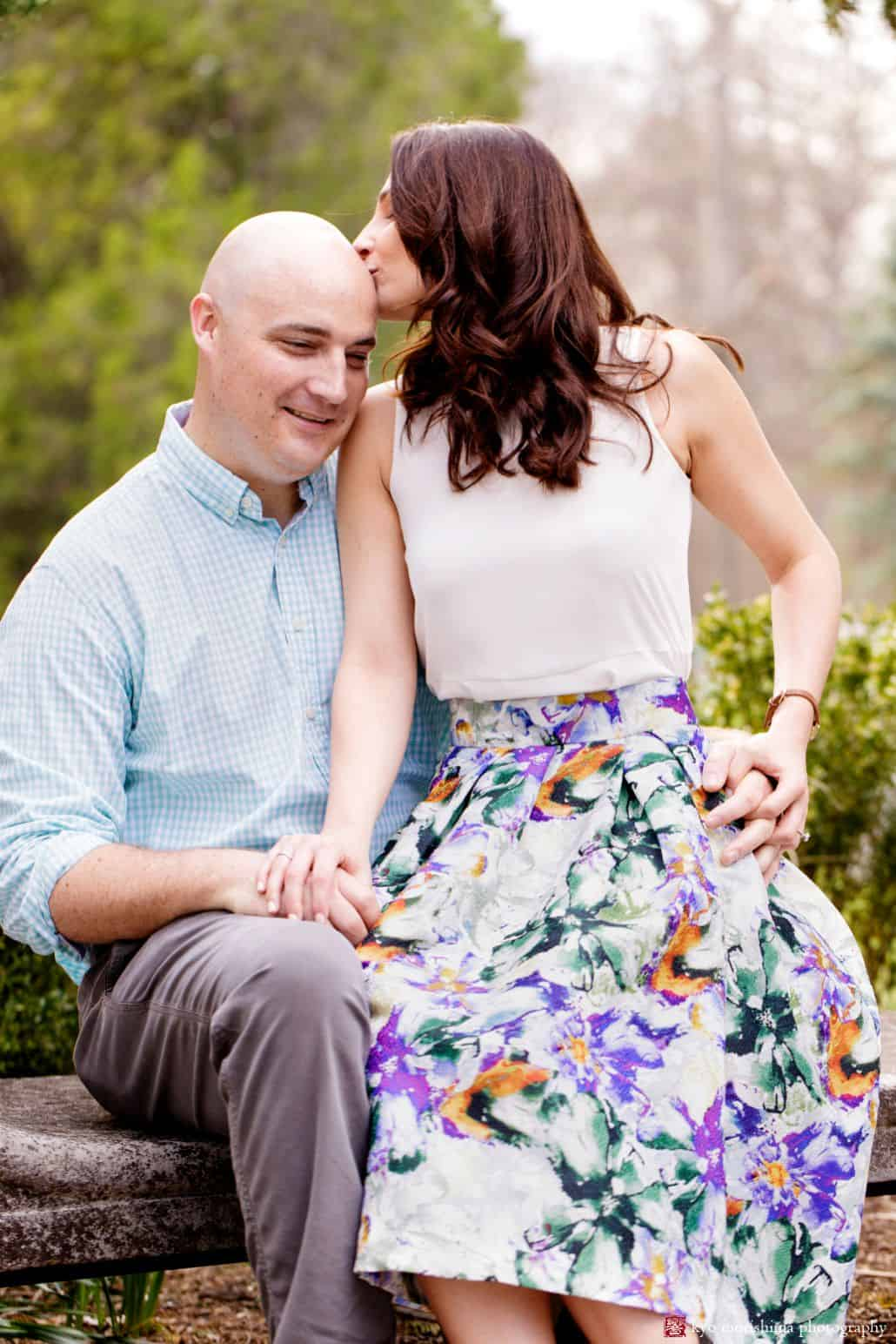 Woman kisses man's head while sitting on stone bench at Hillsborough, NJ engagement photo shoot. Woman wears white blouse and floral skirt. Man wears light blue gingham shirt.