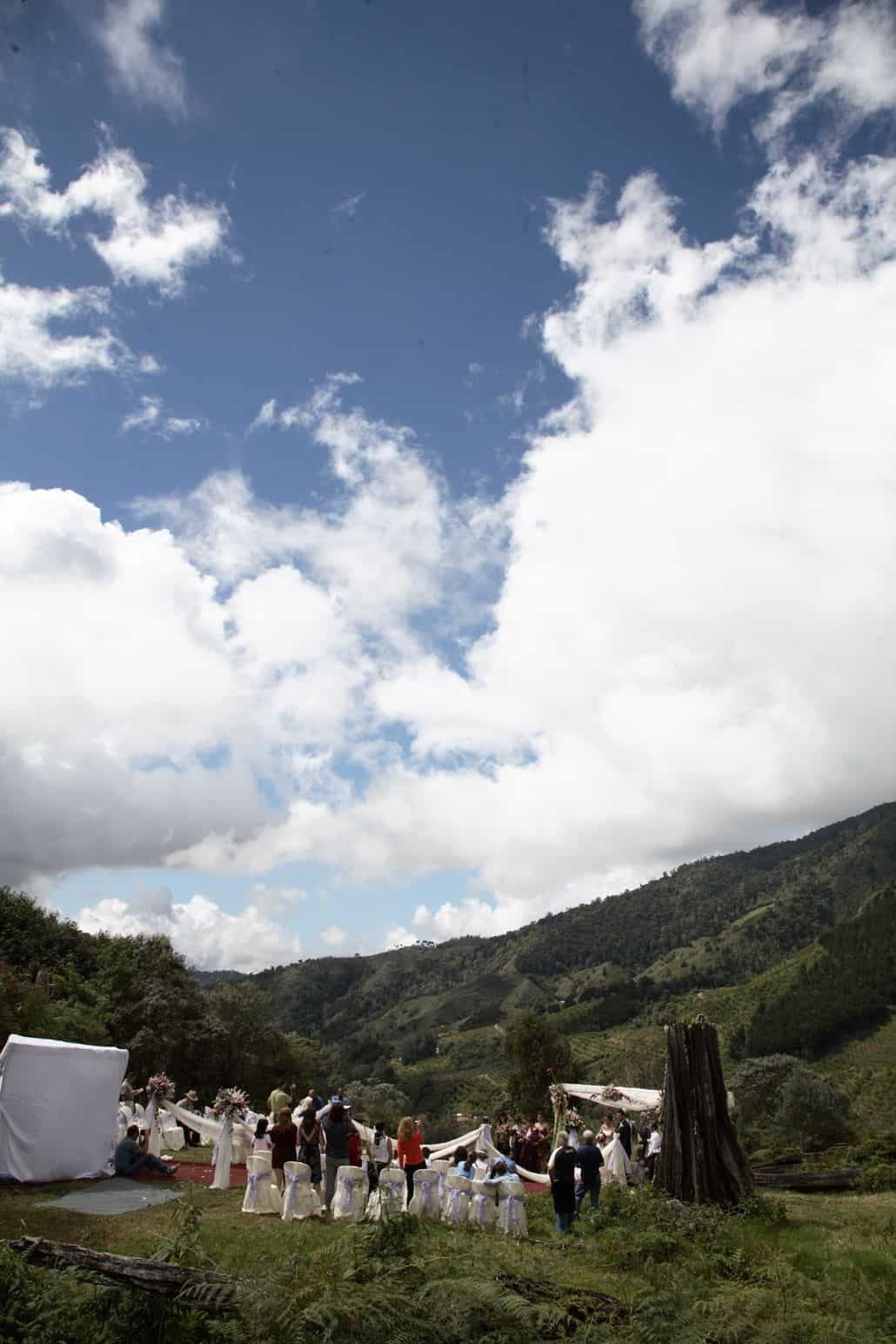 Talamanca cloud forest wedding ceremony, mountain background, white flower topped wedding aisle swags at Costa Rican destination wedding, blue skies and white clouds.