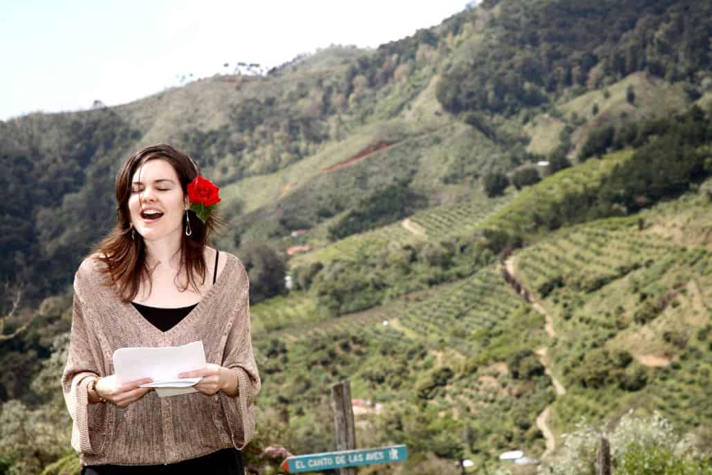 Wedding guest give speech at Talamanca cloud forest wedding ceremony, green mountainside, red rose tucked behind woman's ear. Costa Rican destination wedding photographer.