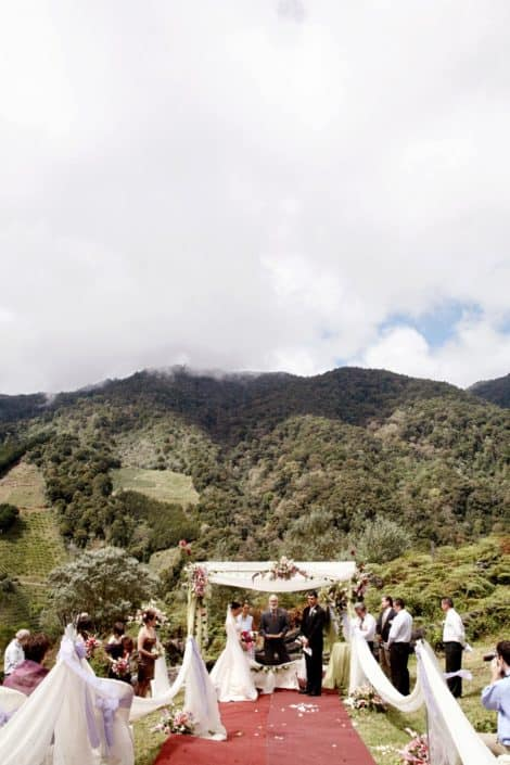 San Gerardo de Dota, Talamanca cloud forest wedding ceremony at Costa Rican destination wedding. Red carpeted aisle, white aisle swag with purple ribbons, bride, groom and wedding party surrounded by green, forest covered mountains.