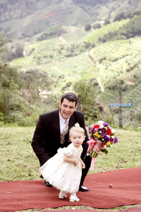 Groom and tiny flower girl on red carpet aisle runner at San Gerardo de Dota, Talamanca clound forest wedding ceremony. Purple, yellow and red bridal bouquet with pink ribbon, green mountaintop, Costa Rican destination wedding photographer.