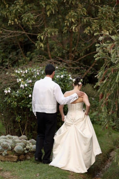 Bride and groom walk into Talamanca cloud forest, groom's hand on bride's shoulder, back laced corset wedding dress, cactus, succulents, rhododendron, flowers in bride's hair. Destination wedding photographer.