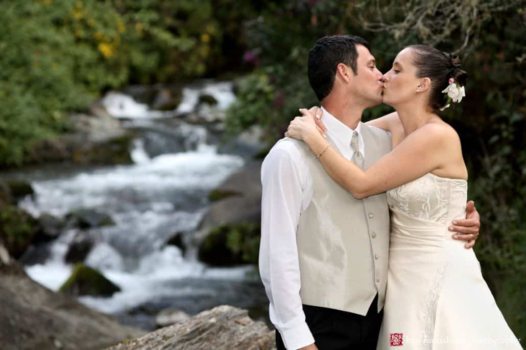 Bride and groom kiss in front of waterfall in Talamanca cloud forest, Costa Rica. Ivory satin wedding dress with white embroidered vines, taupe groom's vest and tie, flowers in brides hair, destination wedding photographer.