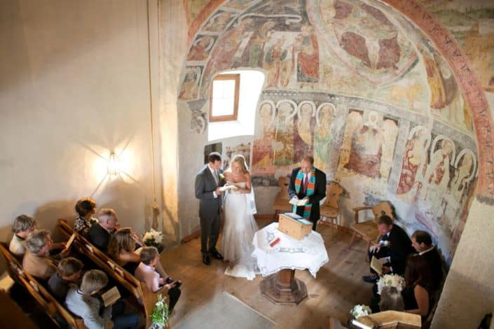 Bride and groom read together in tiny Romanesque church in Swiss Alps during European destination wedding ceremony. Domed alcove with painted mural.