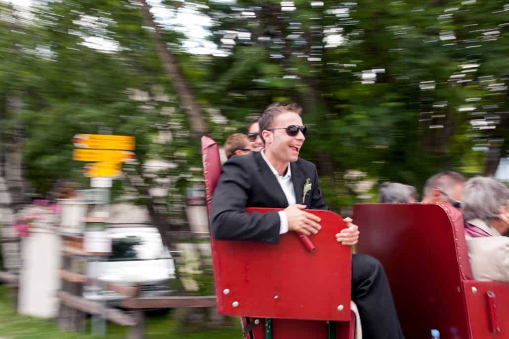 Wedding guests take a ride on red seats in Swiss Alps for European destination wedding photography. Motion photography.