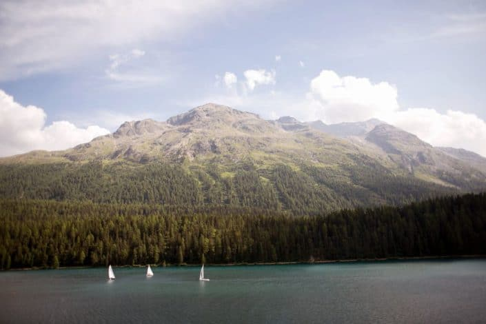 Lake St. Moritz in Switzerland, three sailboats, tree lined Swiss Alps, European destination wedding photography,