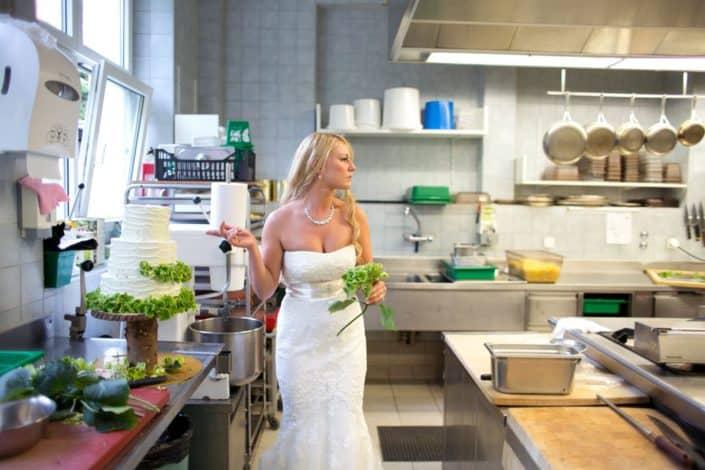 Bride adds green hydrangeas to rustic wedding cake in kitchen at destination wedding at Lake St. Moritz in Switzerland. Gardenias Floral, Waldhaus Hotel.