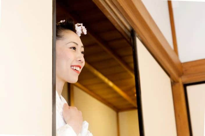 Japanese bride smiles at Heian Shrine in Kyoto, white kimono wedding dress, cherry blossoms in bride's hair, Japan destination wedding photographer.