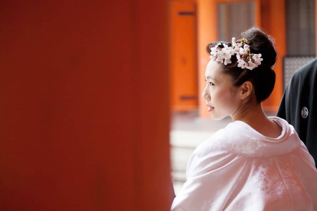 Bride looks over her shoulder at Heian Shrine in Kyoto, Japan. White kimono wedding dress and pink cherry blossoms in bride's hair. vivid orange woodwork. destination wedding photographer.