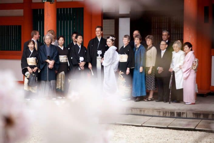 Bride, groom and family pose for wedding picture beyond cherry blossom tree at Heian Shrine in Kyoto, Japan. Bride wears white kimono wedding dress and pink cherry blossoms in her hair, groom wears black Montsuki. Destination wedding photography.