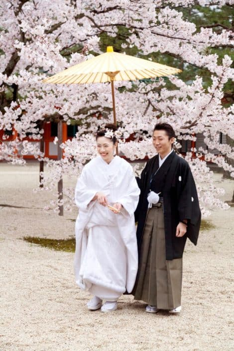 Bride smiles with guest under yellow paper umbrella on gravel path in front of blooming cherry blossom tree in Spring at destination wedding in Kyoto, Japan. Bride wears white kimono wedding dress and cherry blossoms in her hair.