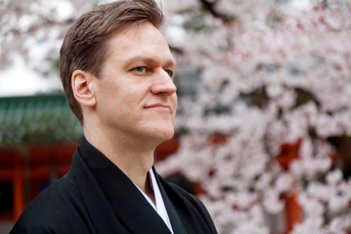 Groom waits for bride at destination wedding at Heian Shrine in Kyoto, Japan. Blooming cherry blossom background, montsuki, Spring Japan destination wedding photographer.