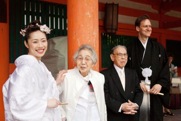 Bride and groom smile with grandparents, grandfather sticks his tongue out, at Heian Shrine in Kyoto, Japan for destination wedding photography. Bride wears white kimono and pink cherry blossoms in her hair, carries fan, groom wears montsuki and carried fan, large orange wooden column background.
