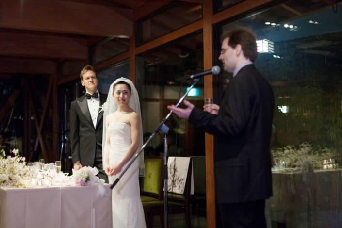 Guest gives speech at destination wedding in Kyoto, Japan, Garden Oriental, now called The Sodoh Higashiyama Kyoto, as bride and groom look on, Bride wears elegant white wedding dress with ruched bodice. floor to ceiling windows, pink and white bouquet.