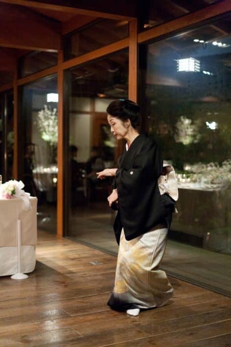 Guest dances in black, ivory and yellow kimono at destination wedding in Kyoto, Japan at Garden Oriental/The Sodoh Higashiyama Kyoto, floor to ceiling windows, destination wedding photography.