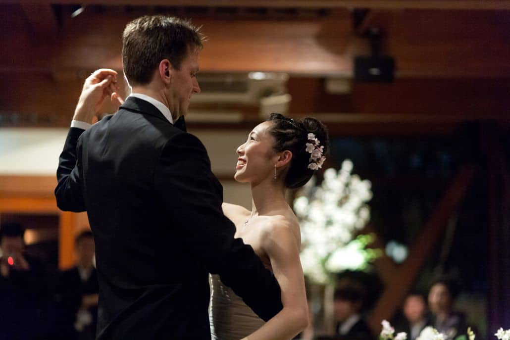 Bride smiles up at groom during their first dance at destination wedding in Kyoto, Japan. Pink cherry blossoms in bride's hair, guests and floral centerpiece in background. The Soduoh Higashiyama Kyoto destination wedding photography.