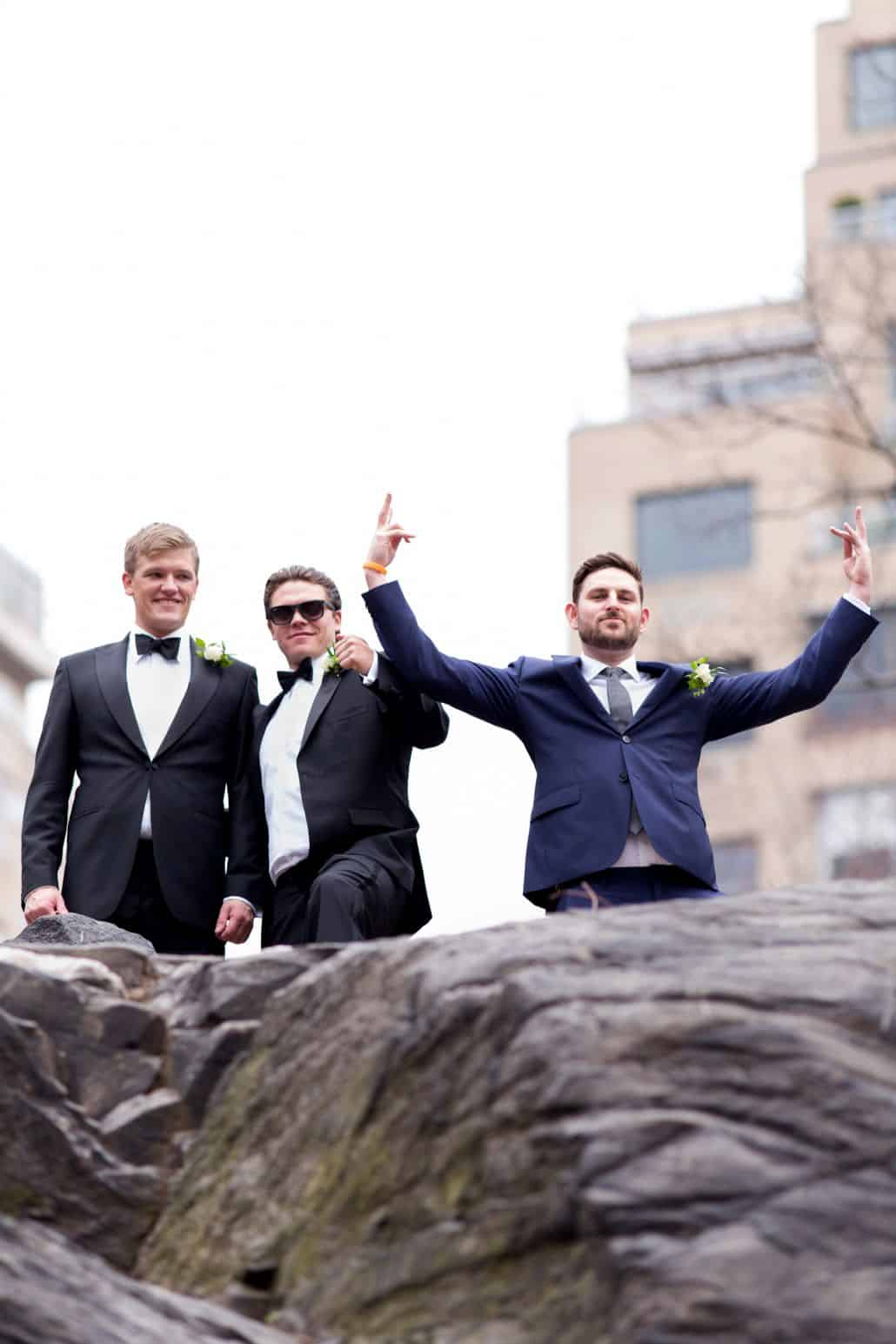 Groom and groomsmen goof around in Central Park Wedding Photo. New York Wedding photographer. Navy suit, black tux.