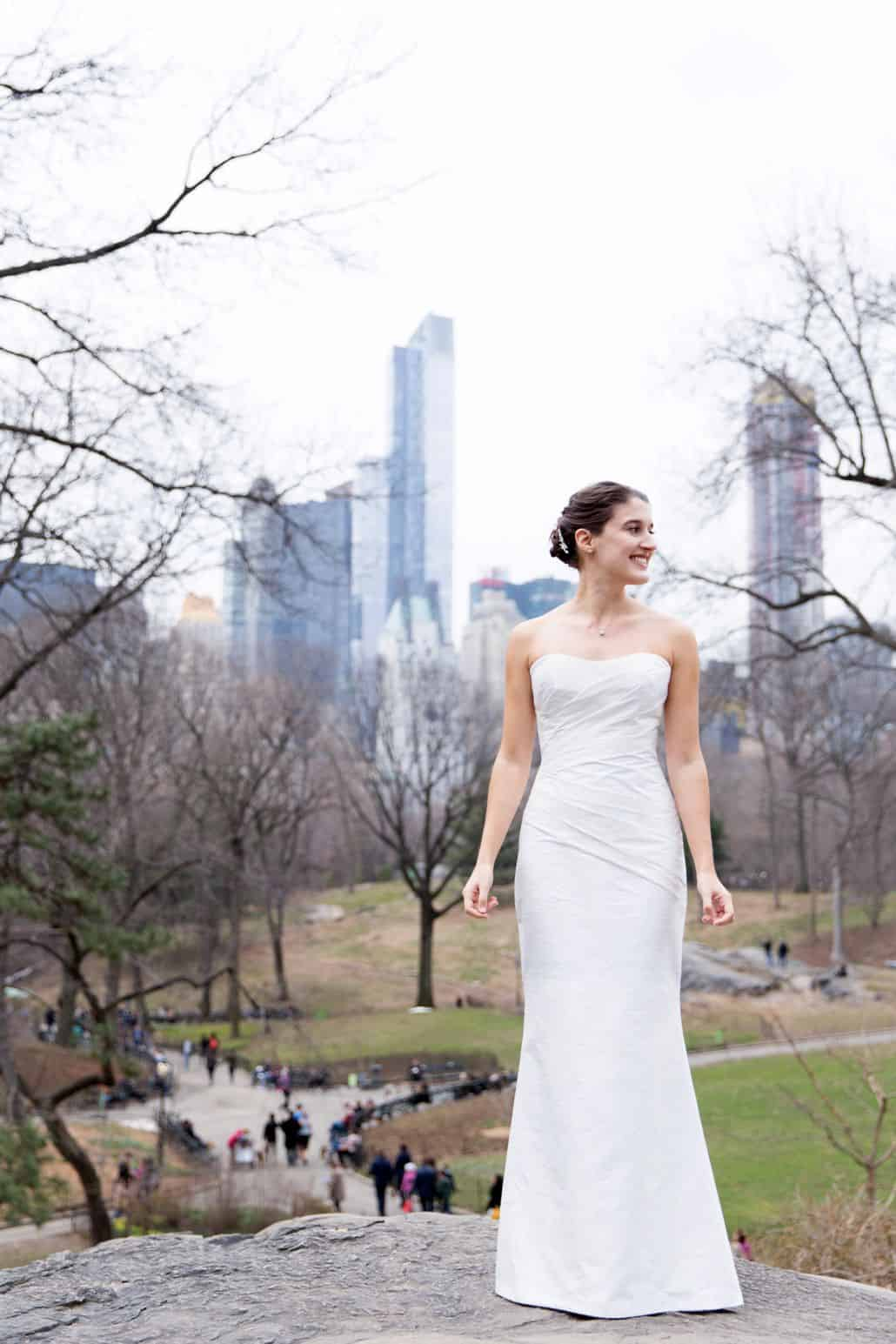 Bride in Central Park for Spring Wedding photo shoot in March in New York. Veka Bridal wedding dress. City skyline and Central Park tree background.