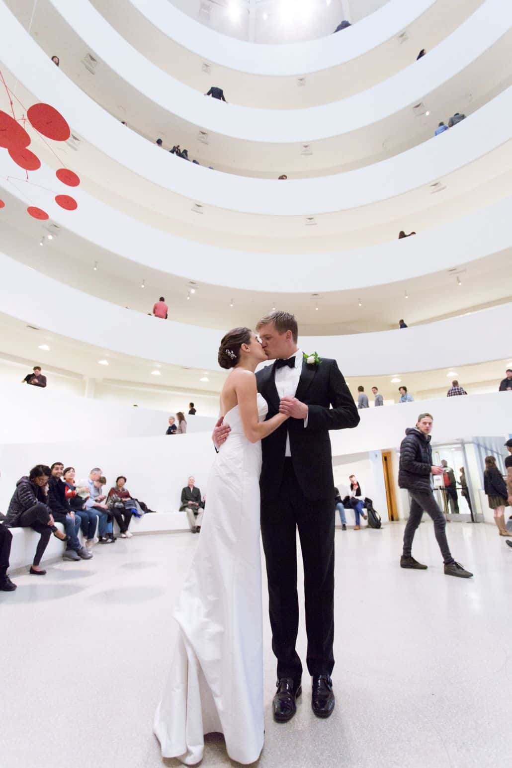 Bride and Groom kiss in middle of Guggenheim where they had their first date. Veka Bridal wedding dress. Black tux. New York wedding photographer. Guggenheim NYC wedding