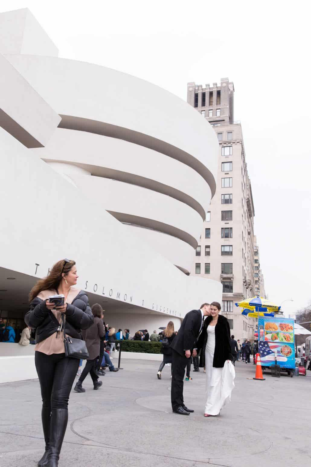 Groom kisses brides cheek in front of Guggenheim in New York as passer-by glances at them over her shoulder. Bride wears black coat over Veka Bridal wedding dress. City skyline and food truck in background. New York Wedding Photographer. Guggenheim NYC wedding