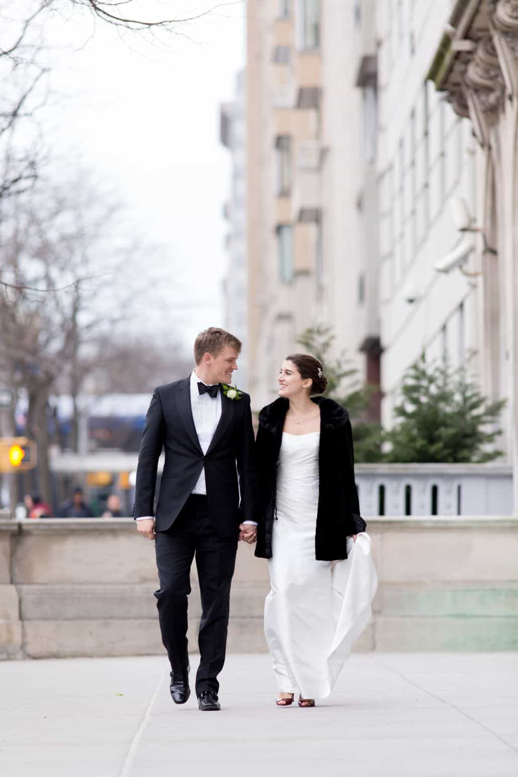 Bride and groom walk hand in hand in New York in front of Guggenheim for early Spring wedding photo shoot in March. Bride wears black coat over Veka Bridal wedding dress. Groom wears black tux.