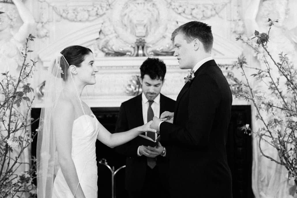 Groom places ring on brides hand during wedding ceremony in front of fireplace in Tennyson Room at Lotos Club Wedding. Veka Bridal wedding dress. Robert Fabrikant wedding rings. Lotos Club Wedding Photos.