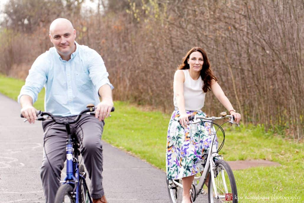 Couple rides bikes side by side in Spring for Hillsborough, NJ engagement photographer. Wooded background. Woman wears white blouse and floral skirt. Many wears light blue gingham shirt and grey pants.