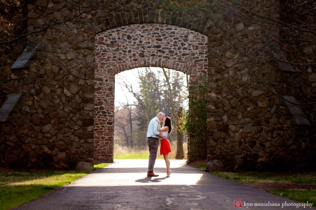 Couple kisses in front of arched, mossy, stone wall doorway for Hillsborough NJ photographer. Woman wears red skirt and white blouse. Man wears light blue gingham shirt and grey pants. French chateau, European estate feel.